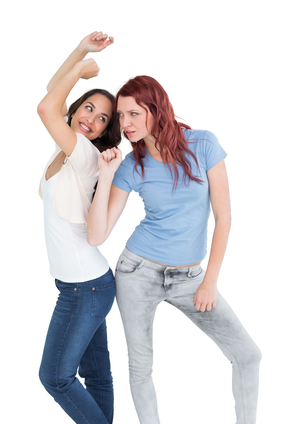 Two cheerful young female friends dancing over white background